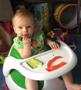 baby eating chicken drumstick, cucumber and red pepper